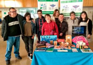 Foto de Familia de usuarios, voluntarios y profesionales de la Asociación PLACEAT en su stand de la I Feria de Voluntariado de la Universidad de Extremadura